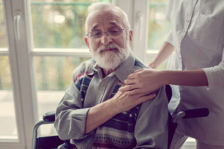 Older sick man sitting on a wheelchair and holding his nurse's hand