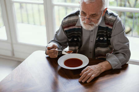 Older sad man eating dinner alone in the apartment