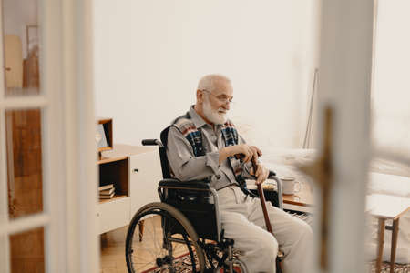 Older disabled man sitting on a wheelchair in his home