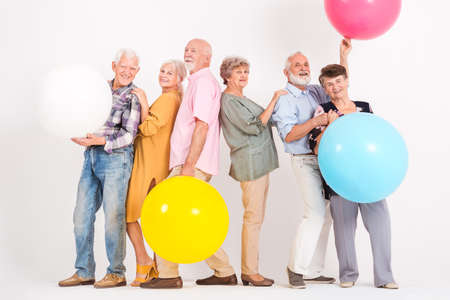Six senior friends with big colorful balloons smiles in empty white interior