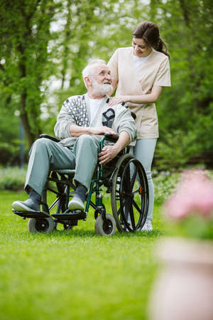 Senior man on the wheelchair in the garden of professional nursing home