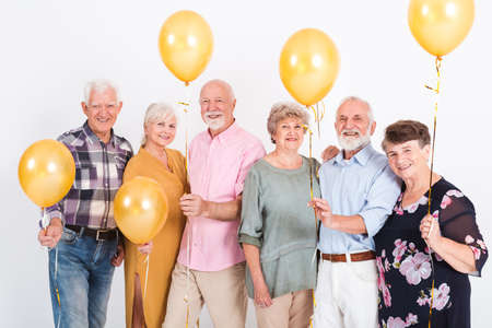 Group of senior people with yellow balloons standing in empty white room