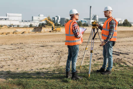 Two road construction workers using measuring device on the field