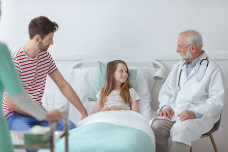 Older doctor and young father visiting little girl in a hospital