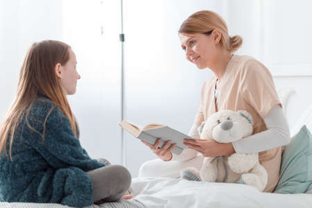 Young nurse reading a book to young sick patient in a hospital