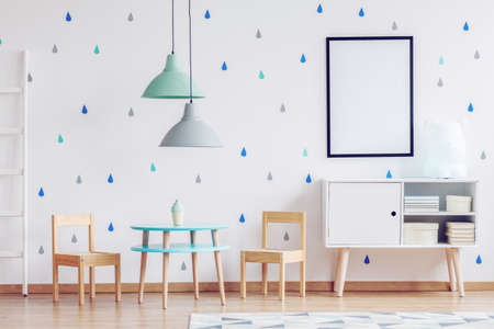 Mockup poster in black frame, pastel colored lamps and wooden furniture in bright kid's playroom interior Stock Photo