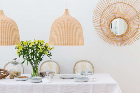 Grey plates, vine glasses and yellow flowers in vase in trendy dining room interior with wicker chandeliers Stock Photo