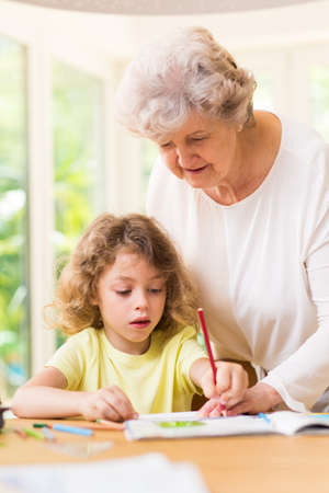 Grandmother painting a picture with paints with her grandson Stock Photo