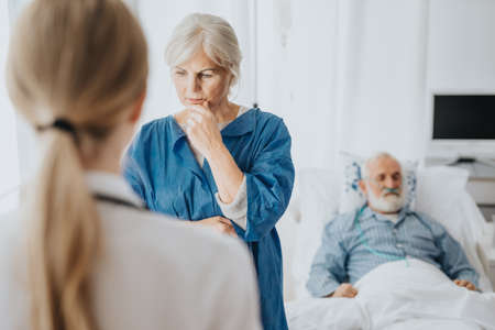 Worried wife staying awake by her passing husband's hospital bed
