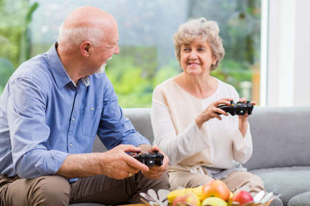 Grandmother and grandfather holding pads and playing video game 스톡 콘텐츠