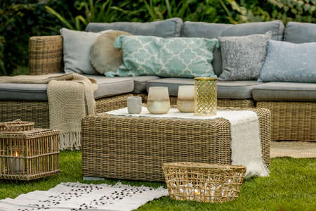 Lanterns, candles and vases on wicker coffee table in front of garden sofa Reklamní fotografie
