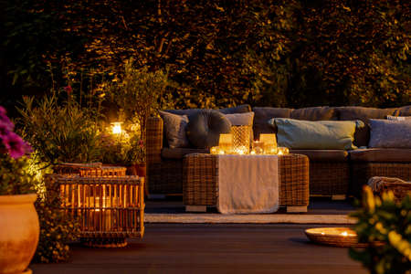 Trendy furniture, lights, lanterns and candles in the garden at night Reklamní fotografie