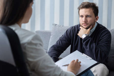 Confident young handsome man during last psychotherapist session with counselor