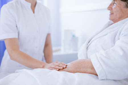Close-up of young nurse holding older sick woman's hand 版權商用圖片
