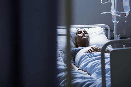 Weak woman with cancer dying alone in hospital bed