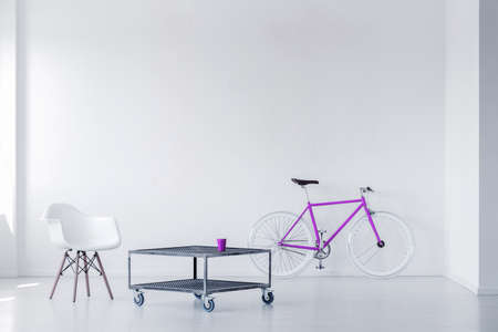 Purple bike, chair and metal coffee table in a minimalistic room interior. Real photo Imagens