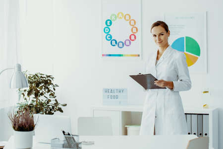 Dietician holding notes and standing in her office