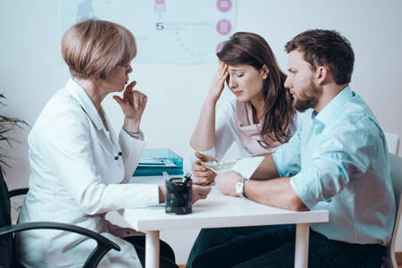 Worried married couple considering In vitro fertility treatment for infertility Stock Photo