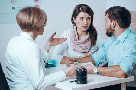 Worried couple consulting with female doctor on medical healthcare therapy Foto de archivo