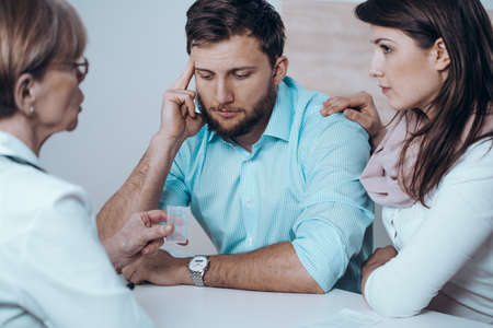 Fertility doctor with man and women together in therapy consult session of inability to get pregnant