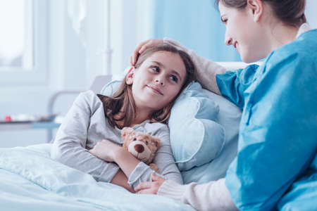 Smiling mother visiting sick daughter in hospital