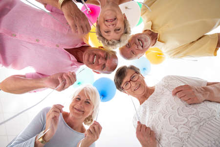 Low angle of happy senior friends in the circle with balloons during birthday party