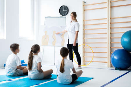 Young physical therapist talking with kids about bad postures
