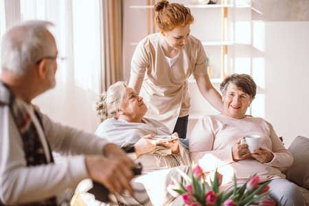 Older happy people spending time together in nursing home with their caregiver