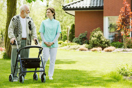 Nurse and patient in the garden of modern senior home with daily care