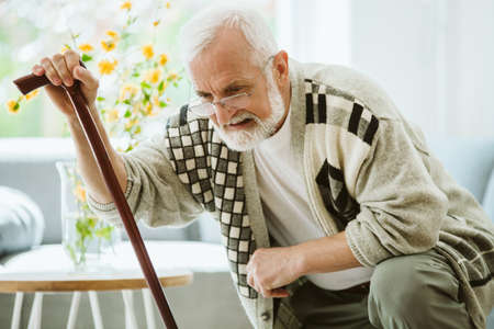Senior man trying to stand up with cane Imagens