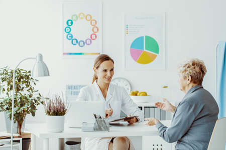 Elderly woman talking to a female doctor at a diet consultation in a privet clinic Stock Photo