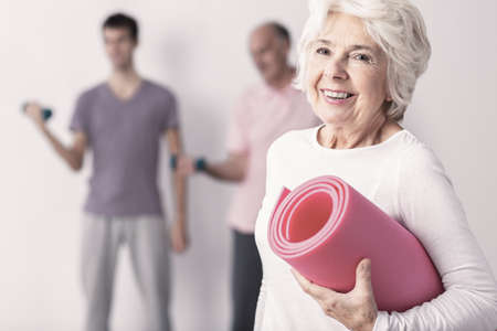 Happy senior woman holding pink joga mat, men exercising in background