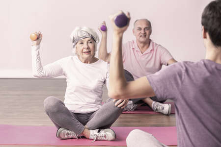 Active seniors sitting on yoga mats lifting the dumbbells during fitness classes