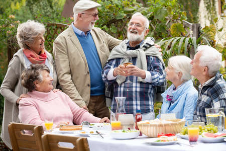 Senior friends laughing together during birthday party in the garden Foto de archivo