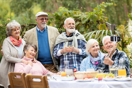 Group of older people taking a picture of themselves during the party