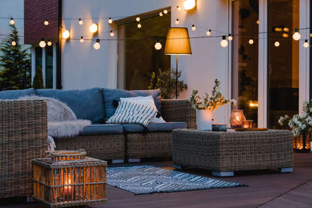 Summer evening on the patio of beautiful suburban house with lights in the garden garden Banque d'images