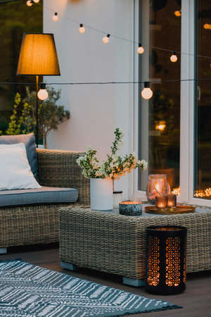 Cozy summer evening on the patio of beautiful suburban house with garden