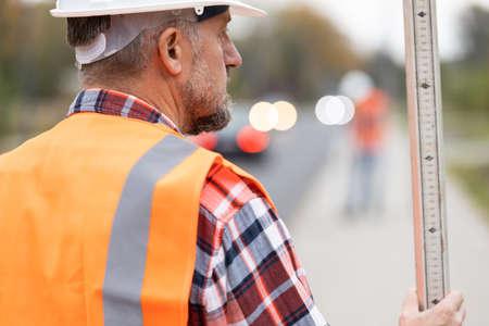 Closeup of road construction worker in orange vest an helmet Standard-Bild