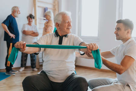 Older man exercising in a gym with young instructor