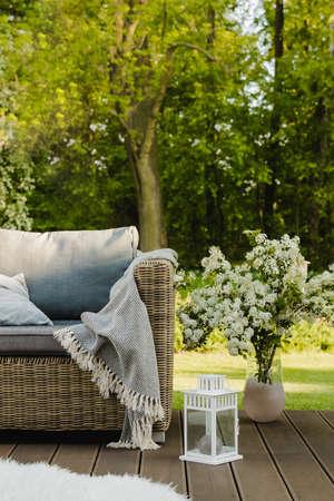 White flowers in vase next to wicker armchair on wooden terrace in green garden Standard-Bild