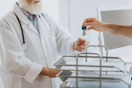 Close-up of male nurse passing the keys to the office to older doctor Standard-Bild