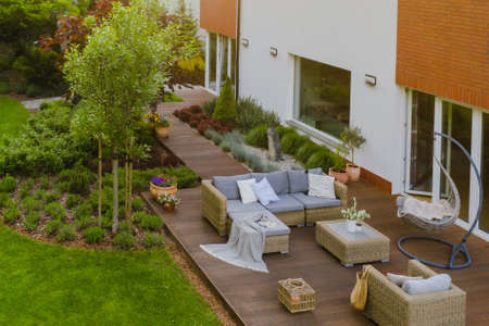 Beautiful green garden with wicker terrace furniture and trees Standard-Bild