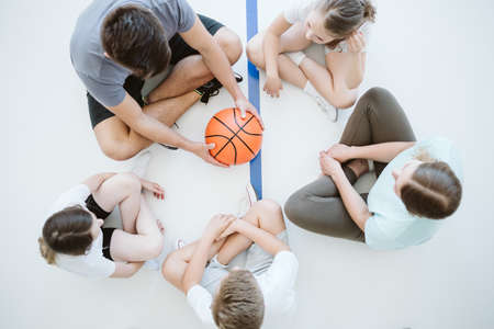 Top view of the children and trainer sitting in a circle on the gym floor before the basketball game Standard-Bild