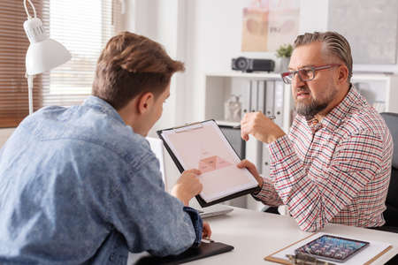 Middle aged therapist talking with his young client about life balance Standard-Bild