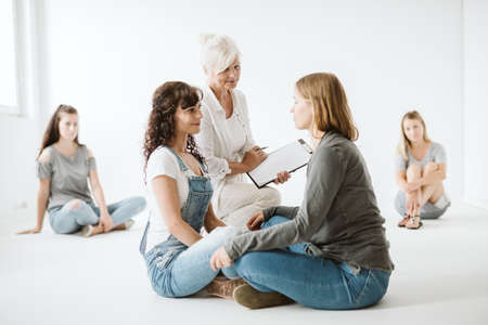 Two women exercising together during group psychotherapy