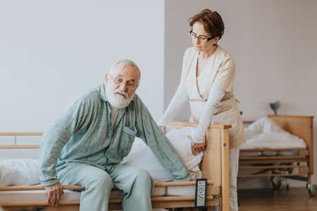 Helpful nurse in a beige uniform helps the patient in a blue pajamas getting up from bed Standard-Bild
