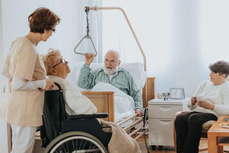 Senior people visiting injured friend in the hospital Standard-Bild