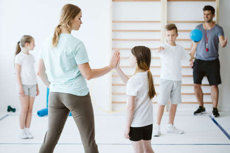 Girl doing high five with her teacher during physical education at school