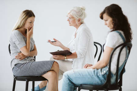 Young worried woman talking about her problems with psychotherapist Standard-Bild