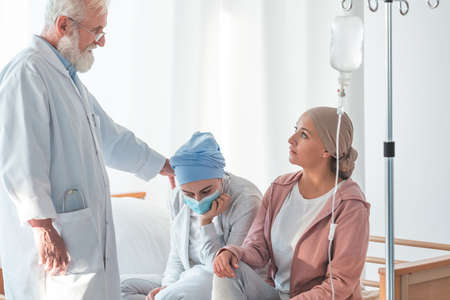 Older doctor supporting two patients suffering from cancer